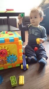 Avant 3 ans, l'enfant a essentiellement besoin d'interagir avec son environnement. Il construit ses repères à travers les histoires, les jeux, la musique... Comme Léo, 15 mois qui s'amuse beaucoup avec ses gros cubes au milieu du salon !
